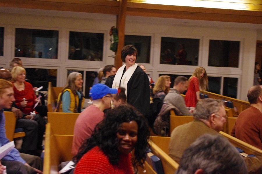 Pastor Trina in the middle of the sanctuary among pews with worshipers