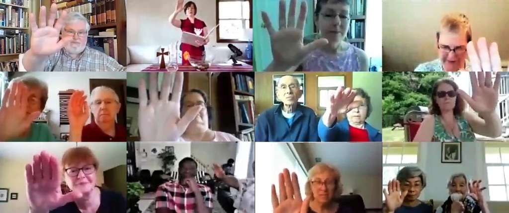 Image of Zoom screen with elders in different households raising their hands out during ordination of new deacons and elders