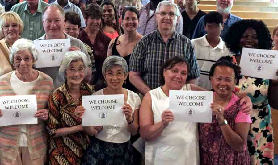 """Church members holding signs saying """"We Choose Welcome."""""""