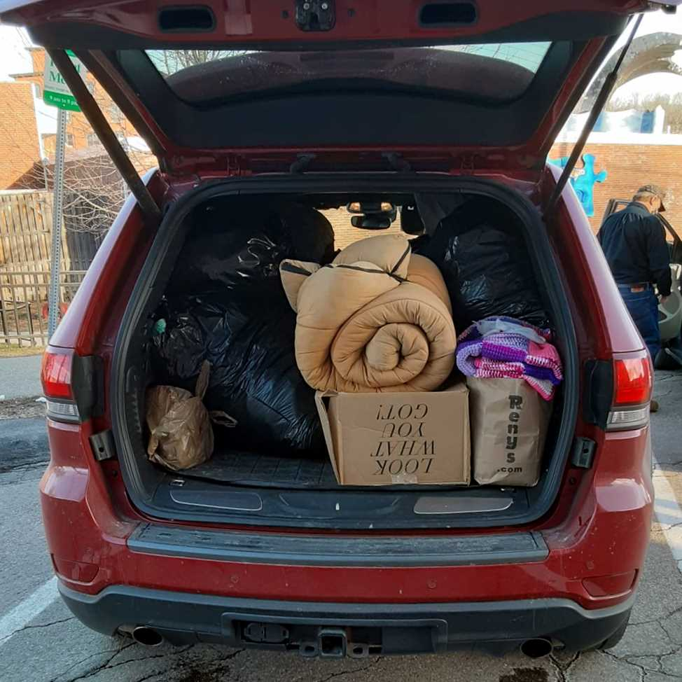 Back of SUV packed with bags of warm clothing