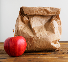 Brown bag lunch and apple.