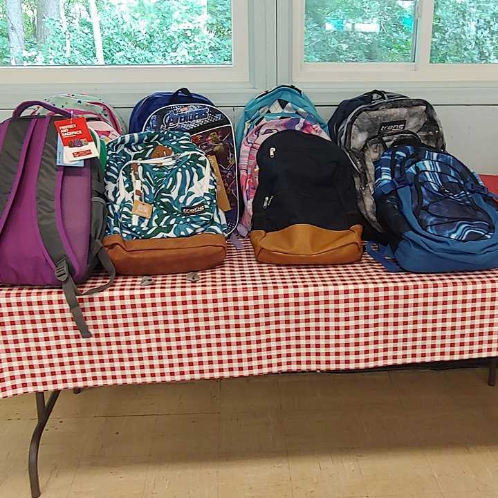 Backpacks piled on table