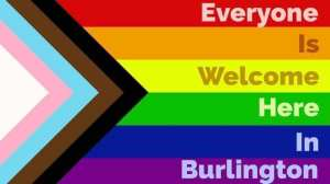 """Rainbow flag with text """"Everyone is Welcome Here I n Burlington"""