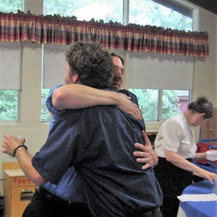 Men hugging in Fellowship Hall
