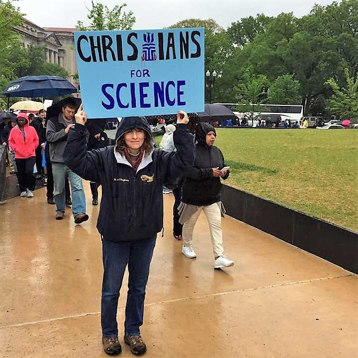 """Person holds sign saying """"Christians for Science""""go"""